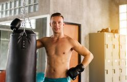 Sporty man boxer relax after punching at a boxing gym,Strong men boxer training on punching bag royalty free stock images