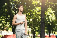 Man choose music to listen during workout. Sporty man choose music to listen in his mobile phone during workout in park, copy space Stock Photography