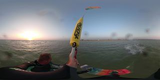 A man at dawn rides on the waves driving a training kite, 360 degrees. A sporty man in a diving suit manages a training kite on the sea stock video