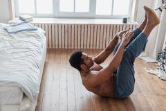 Sporty man doing abs workout. ,Training indoors. Young attractive muscular man doing morning exercise in the bedrooom, spare time, side view full length photo stock photography