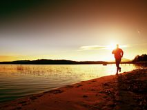 Sporty Man doing Morning Jogging on Sea Beach at Bright Sunrise Silhouettes Royalty Free Stock Image
