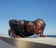 Sporty man doing push-ups outdoors Stock Photos