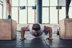 Sporty Man Doing Push Ups Between Two Athletes stock images