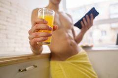 Sporty man drinking orange juice using mobile app royalty free stock image