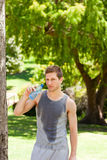 Sporty man drinking water in the park Stock Image