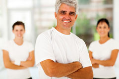 Sporty man family. Smiling middle aged sporty men with arms folded in front of family at home royalty free stock image