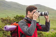 Sporty man on a hike taking a photograph Stock Image