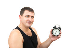 Sporty man holds alarm clock Royalty Free Stock Photography