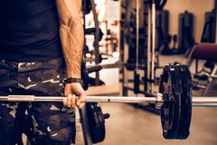 Sporty man holds barbell in gym close. Close up of arm of young fit man doing barbell exercises in gym. Healthy lifestyle concept Stock Photography