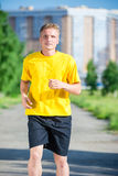 Sporty man jogging in city street park. Outdoor fitness. Royalty Free Stock Photo
