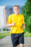 Sporty man jogging in city street park. Outdoor fitness. Stock Image