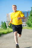 Sporty man jogging in city street park. Outdoor fitness. Stock Images