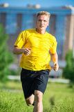 Sporty man jogging in city street park. Outdoor fitness. Royalty Free Stock Photos