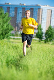 Sporty man jogging in city street park. Outdoor fitness. Royalty Free Stock Photography
