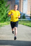 Sporty man jogging in city street park. Outdoor fitness. Royalty Free Stock Image