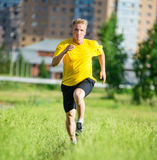 Sporty man jogging in city street park. Outdoor fitness. Stock Photos
