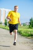 Sporty man jogging in city street park. Outdoor Stock Photos