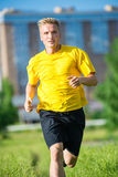 Sporty man jogging in city street park. Outdoor Stock Images