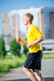 Sporty man jogging in city street park. Outdoor Stock Photos
