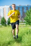 Sporty man jogging in city street park. Outdoor Royalty Free Stock Photo