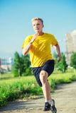 Sporty man jogging in city street park. Outdoor Royalty Free Stock Image