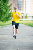 Sporty man jogging in city street park. Outdoor Stock Photography