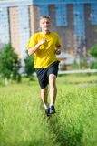 Sporty man jogging in city street park. Outdoor Stock Image