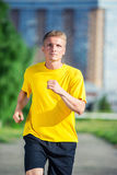 Sporty man jogging in city street park. Outdoor Royalty Free Stock Photography