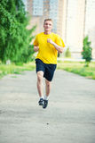 Sporty man jogging in city street park. Outdoor Royalty Free Stock Images