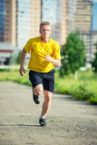 Sporty man jogging in city street park. Outdoor Stock Photo
