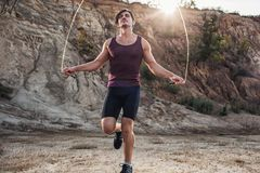 Sporty man jumping rope outdoors Royalty Free Stock Photography