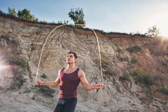 Sporty man jumping rope outdoors. In the morning stock image