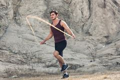 Sporty man jumping rope outdoors. In the morning royalty free stock images