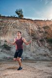 Sporty man jumping rope outdoors Royalty Free Stock Images