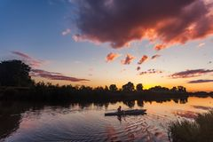 Sporty man kayaking on river surrounded by forest at sunset stock images