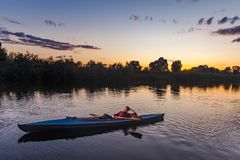 Sporty man kayaking on river surrounded by forest at sunset royalty free stock image