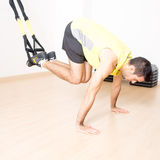 Sporty man makes legs suspension training Stock Image