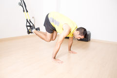 Sporty man makes legs suspension training Royalty Free Stock Photos
