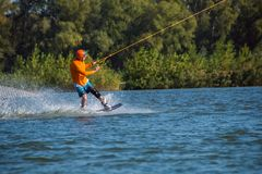 Sporty man  is engaged in wakeboarding. Sporty man, in orange shirt and helmet, is engaged in wakeboarding in cable park on a sunny day. Active vacation in Royalty Free Stock Images