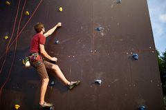 Sporty man practicing rock climbing in gym on artificial rock training wall outdoors. Young talanted slim climber guy on. Sporty man practicing rock climbing in Royalty Free Stock Photography