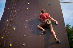 Sporty man practicing rock climbing in gym on artificial rock training wall outdoors. Young talanted slim climber guy on. Sporty man practicing rock climbing in Stock Photography