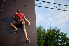 Sporty man practicing rock climbing in gym on artificial rock training wall outdoors. Young talanted slim climber guy on. Sporty man practicing rock climbing in Stock Images