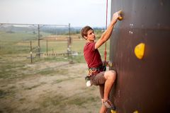 Sporty man practicing rock climbing in gym on artificial rock training wall outdoors. Young talanted climber guy on. Sporty man practicing rock climbing in gym Royalty Free Stock Photos