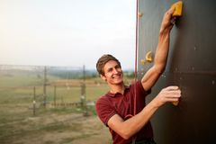 Sporty man practicing rock climbing in gym on artificial rock training wall outdoors. Young talanted smiling climber guy. Sporty man practicing rock climbing in Stock Images