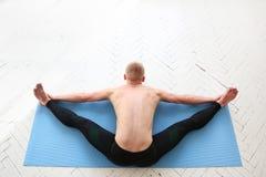 Sporty man practicing yoga. Asana Kurmasana. Tortoise pose. Tortoise posture. Stock Image