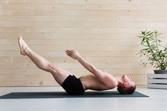 Sporty man practicing yoga stock photography