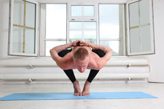 Sporty man practicing yoga. Squat, Garland pose, Malasana. Sporty man practicing yoga. Sitting in squat, Garland pose, Malasana Stock Photo