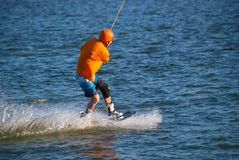 Sporty man prepares for a wakeboard trick. During training in the cable park on a sunny day. Active vacation in outdoor Stock Photos