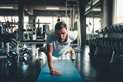 Sporty man push-up exercising by one hand in fitness gym., Portrait of young handsome man working out against on sport. Bodybuilding equipment background royalty free stock photography