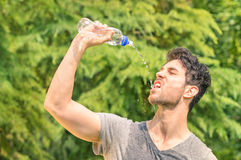 Sporty man refreshing with cold water after run training royalty free stock image